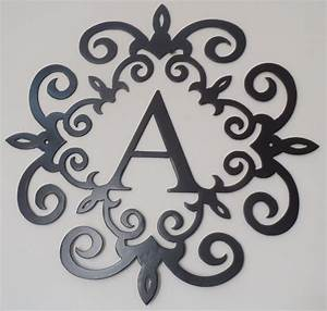 family initial monogram inside a metal scroll with a With metal monogram letters wall art