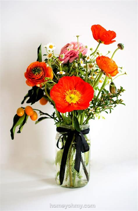 flower arranging ranunculus poppies  kumquats diy