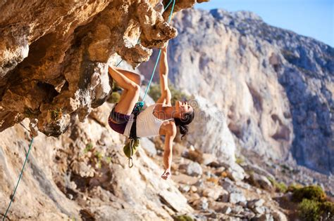 Young Woman Lead Climbing Overhanging Cliff Stock Photo