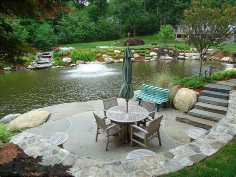 blustone slab pond patio with waterfall and landscaping by