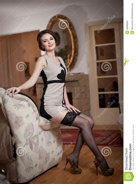Animal Print Sofa by Happy Smiling Attractive Woman Wearing An Elegant Dress