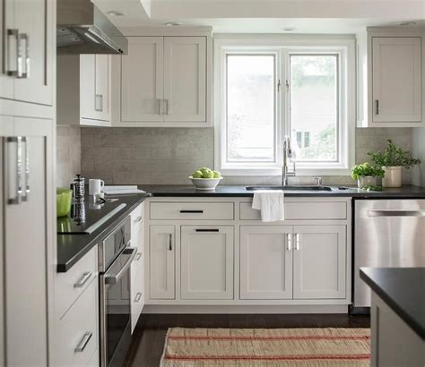 chic kitchen features extra light gray cabinets paired  black quartz countertops