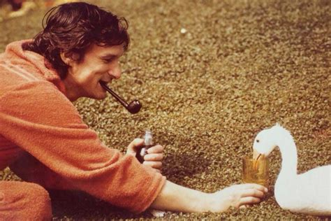 A young Hugh Hefner, with pipe, feeding a goose ...
