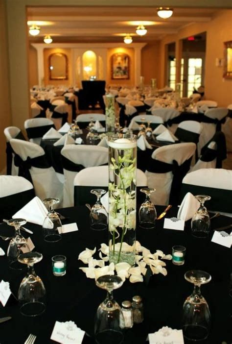 black tablecloths  white draped chairs  black bows