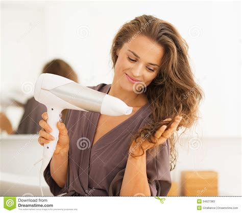 happy woman blow drying hair  bathroom stock image