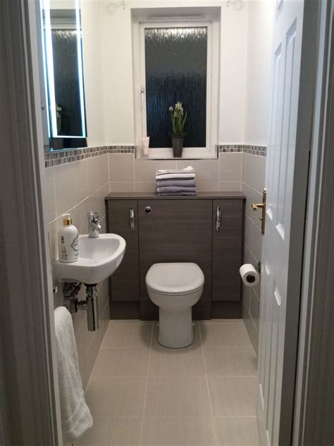 small cloakroom grey lined wall  floor tiles edged
