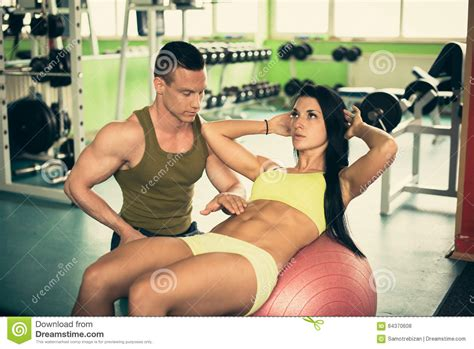personal fitness coach trains beautiful woman  gym stock