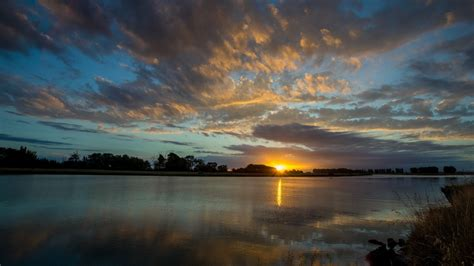 1366x768 Calm Lake Trees Shore Sunset desktop PC and Mac