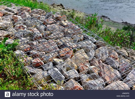 rock walls in wire mesh river embankment reinforced with gabion wire mesh baskets filled with stock photo royalty free