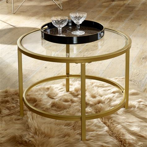 A table has a base of 2 crossed panels. Vintage Gold Round Glass Top Coffee Table - Melody Maison®