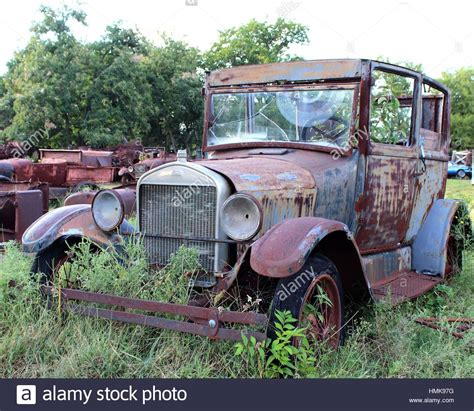 Weathered And Broken Old Cars And Trucks Rusting Away In
