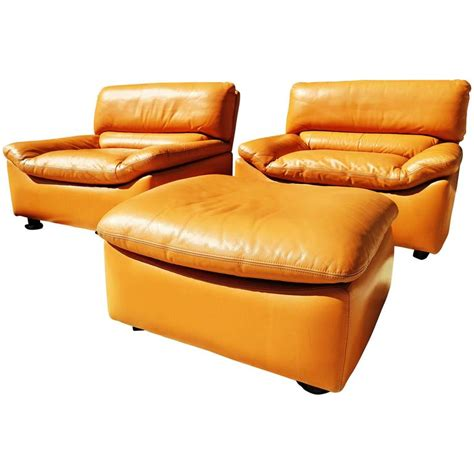 pair of leather lounge chairs with ottoman by