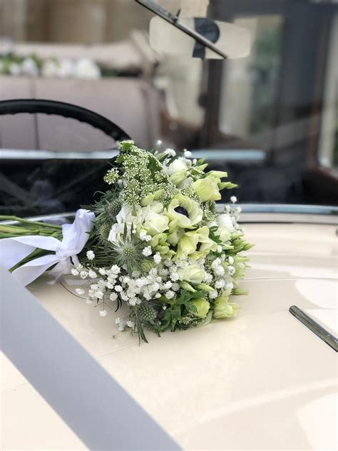 white bridal bouquet on vintage rolls royce wedding
