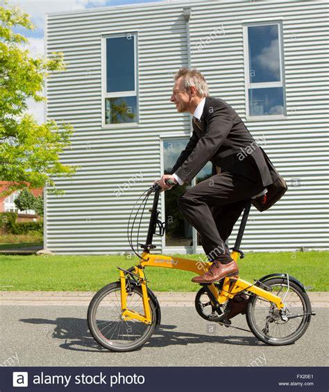 Bike To Work 1 businessman on a folding bike to work stock photo