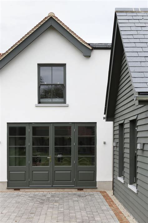 white home exterior dark green trim brick border   driveway ham interiors house