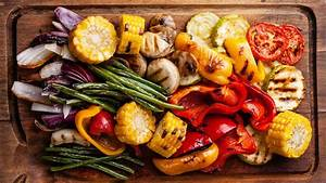 pile of grilled vegetables sits on a wooden cutting board
