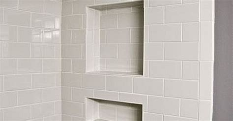 white subway tile featuring shower niche and bullnose edge