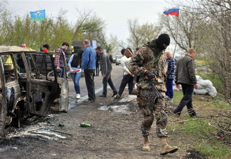 An Armed Pro Russian Militant Looks For Ammunition Casings