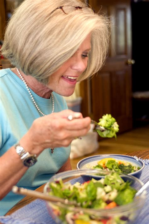 picture woman eating vegetable salad packed full