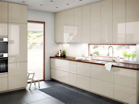 cuisine de taille moyenne avec portes et tiroirs en beige clair brillant et plan de travail en