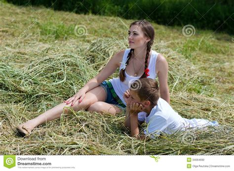 Teenage Sister And Little Brother Sitting On Hay Stock
