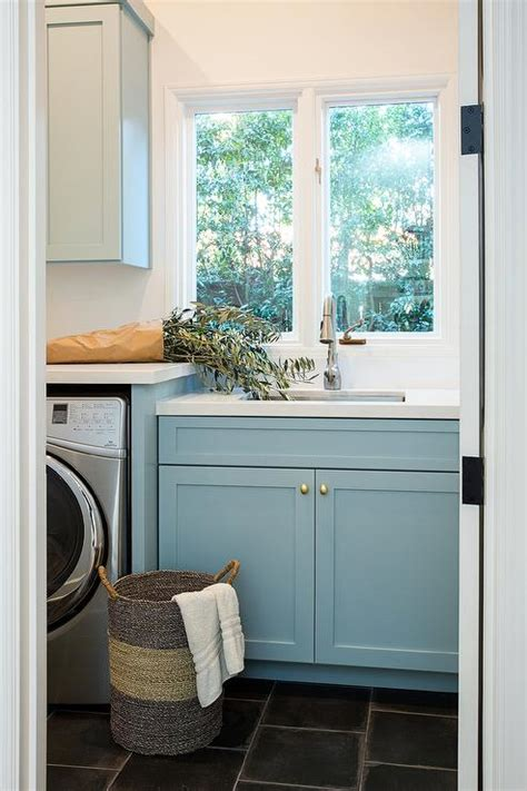 blue laundry room cabinets  oval brass knobs  slate