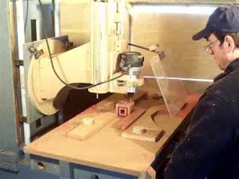 wooden charging station router wood milling machine cutting out a cube within a