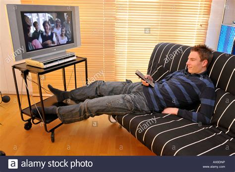 Teenager Sitting On Couch Watching Tv Stock Photo
