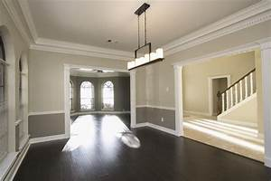 two tone wall with chair rail and dark hardwood dining With two tone dining room color ideas