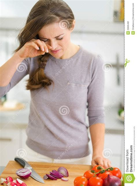 Young Housewife Crying While Cutting Onion Stock Image