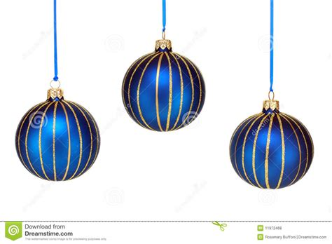 three blue and gold christmas ornaments on white royalty