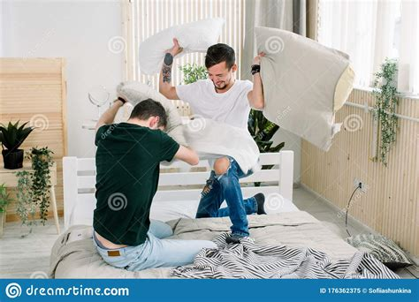 Portrait Of Young Gay Couple Having Pillow Fight In
