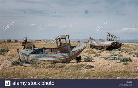 Old Boat Washed Up by Old Abandoned Boats Washed Up On A Beach Stock Photo