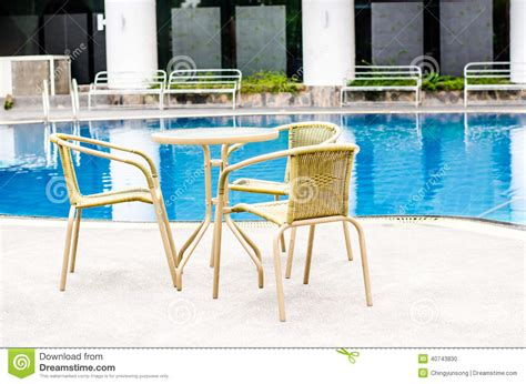 table and chairs with swimming pool stock photo image