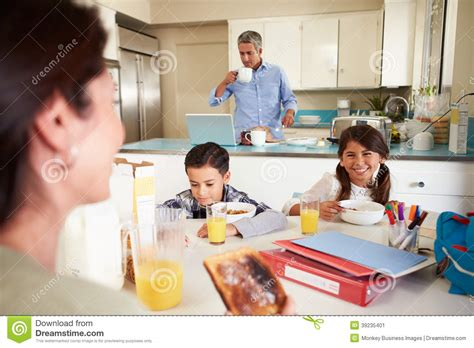 Hispanic Family Eating Breakfast At Home Before School Stock Image