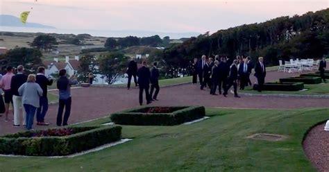 trump donald mirror away golf secret service paraglider course agents scottish run walk surrounded around running flies protester turns runs