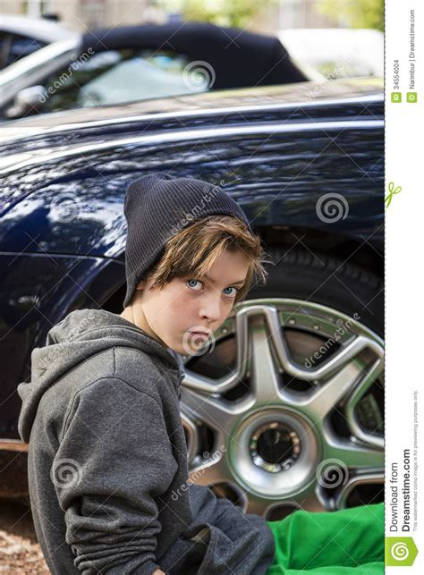Cool Teenage Boy Sitting In Front Of A Rim Of Wheel Stock