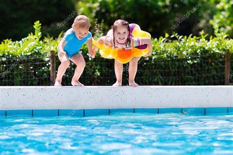 Kids jumping into swimming pool — Stock Photo © FamVeldman ...