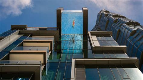 transparent infinity pool hangs  condo towers edge