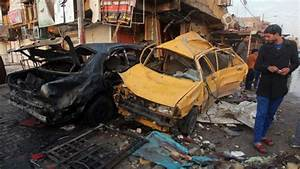 Iraqis inspect the aftermath scene of a car bomb attack in ...