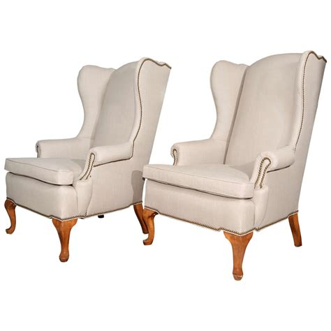 pair of grey linen and nailhead wing chairs