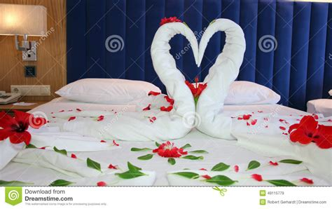 bedsheet hotel flower petal arrangement on a hotel bed stock