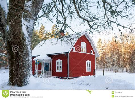red painted swedish wooden house   wintry landscape