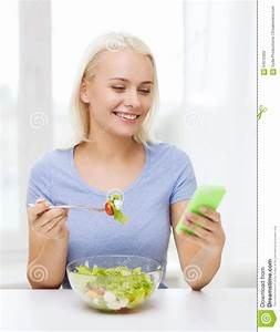 Smiling Woman With Smartphone Eating Salad At Home Stock ...