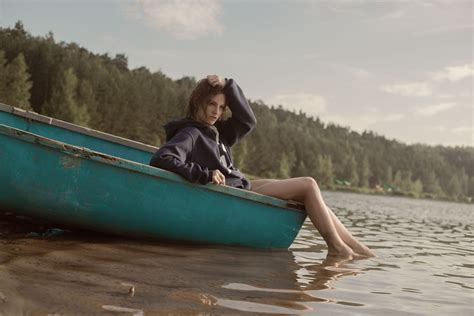 Girls On Boats woman in black hoodie in teal canoe in body of water