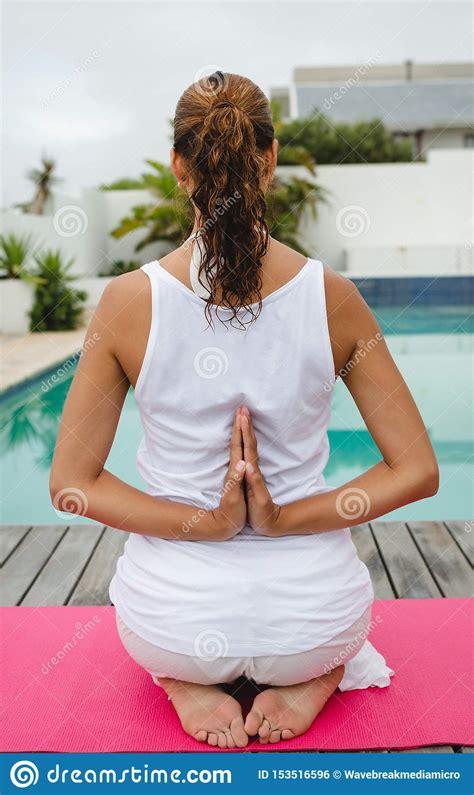 Woman Performing Yoga Near Swimming Pool In The Backyard