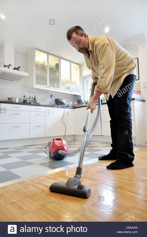 kitchen floor vacuum middle aged using vacuum cleaner on the wooden floor 1684
