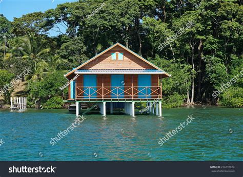 Bungalow Over Water With Tropical Vegetation In Background