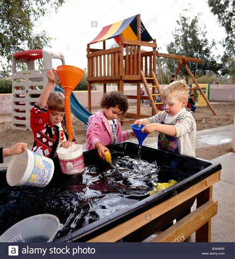 children at a water table in an arizona 777 | young children playing at a water table game in an arizona preschool B34WNF