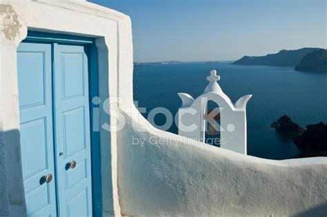 blue door white wall bell tower  aegean sea stock